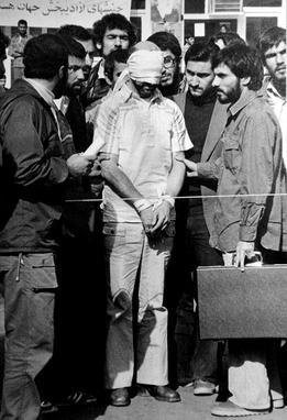 Gijzelaar Barry Rosen, tijdens een van de 'optredens' van de gijzelaars. De man met de koffer is volgens sommige oud-gijzelaars de latere Iraanse president Mahmoud Ahmedinejad, hoewel dat officieel door alle betrokkenen wordt ontkend. bron: wikimedia commons